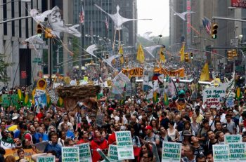 Demonstrators make their way down Sixth Avenue in New York during the People's Climate March Sunday, Sept. 21, 2004 (AP Photo/Jason DeCrow)